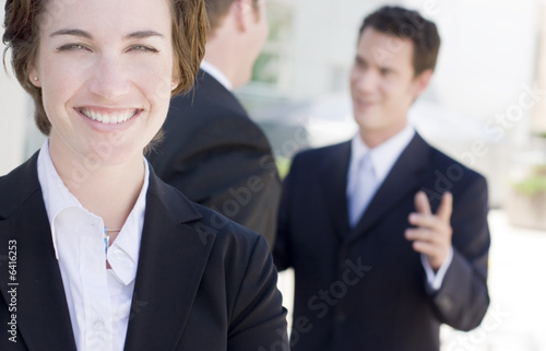 business woman with two businessmen talking in background