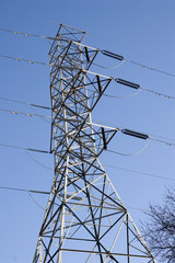 A hgh power tower against blue with cables and trees