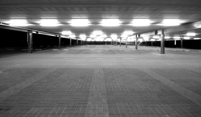 an empty spacious parking lot by night in black and white