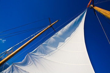 Yacht sail and blue cloudless aky above