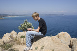 teen sitting on rocks poster