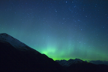 Northern lights making the sky green over the tops of mountains