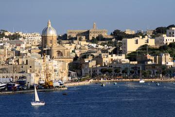 vista della costa maltese con barca a vela bianca