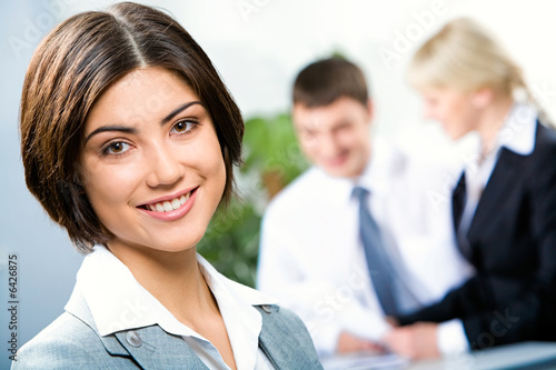 Face of beautiful woman on background of business people