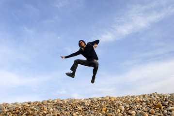 young man jumps on beach, with the sky as background