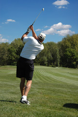 Golfer in the after swing looking on a beautiful sunny day