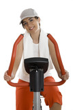 Young woman training on exercise bike at the gym poster