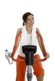 Young women training on exercise bike at the gym  poster