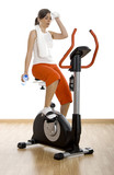 Young woman tired of training on exercise bike at the gym poster