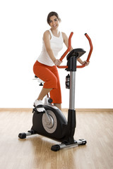 Young woman training on exercise bike at the gym