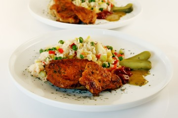 Fried slices of pork decorated with vegetable risotto