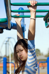 young girl on monkey bars in a school playground