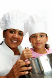 Woman with child teaching her to cook poster
