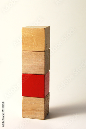 Four wooden toy blocks one in red