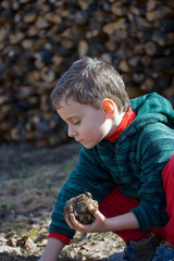 Child modeling with mud with a stack of logs in the background