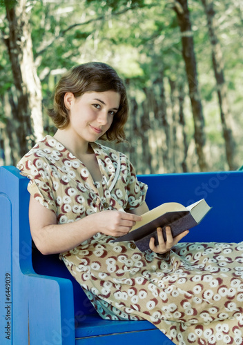 Pretty young woman/girl reading a book outdoors