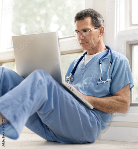Doctor Reviewing His Notes on Laptop