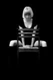 Blonde with a passionate sight sits on a chair. Monochrome poster