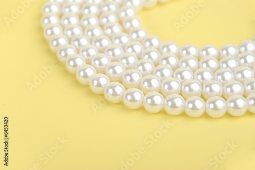 Pearl necklace isolated on yellow background.