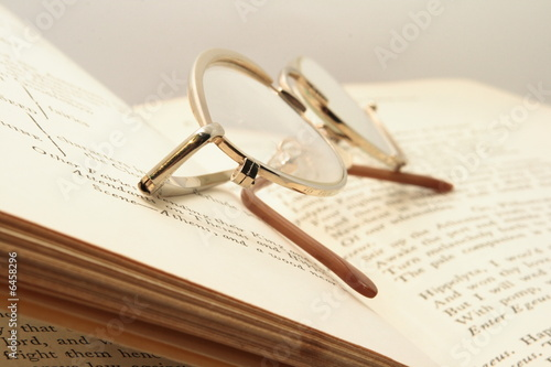 Pice of book and brown glasses