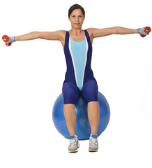 Woman doing bar-bells exercise while is sitting on a gym ball.