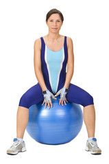 Young woman sitting on a fitness blue ball.