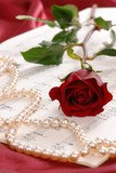 Red rose and string of pearls lying on sheet music poster