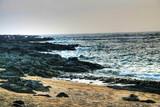Lava rocks along a dark turquoise ocean poster
