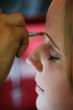 A young woman has makeup applied before a big event