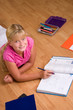 Cute blonde girl doing her school homework.