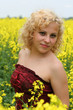 Beautiful young girl with field of nice yellow flowers