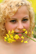 Girl holds in mouth canzola flower - very nice portrait