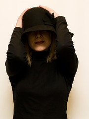 mistery woman holding her hat on white background