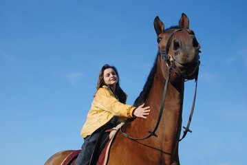 Young woman riding on big brown horse with clear blue sky