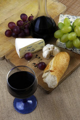 Romantic dinner with wine and cheese on rustic board