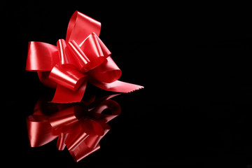 red bow standing on a black with reflections2.