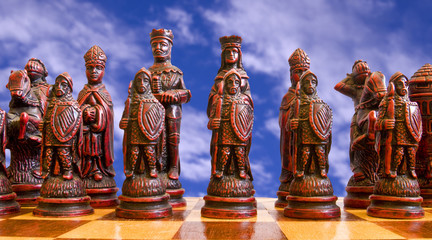 Red chess pieces pictured against a cloudy sky..