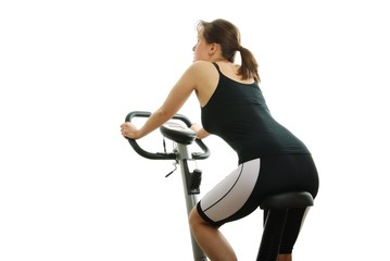 Isolated young woman riding on a spinning bicycle from back