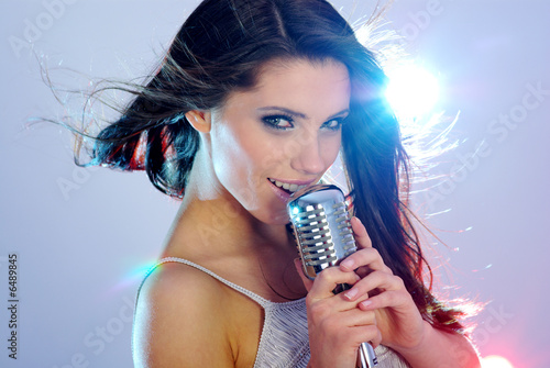 Rock star. Young woman with retro music micropone