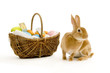 Rabbit next to a basket filled with chocolate easter eggs