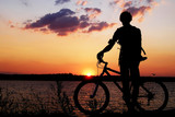 Silhouette of a cyclist admiring the sunset. poster