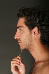 Man pulling his beard with tweezers