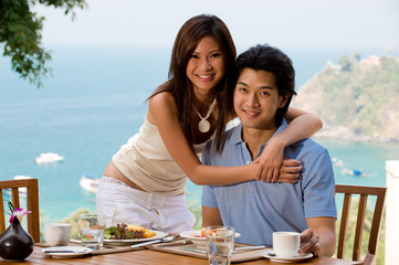 A young Asian couple sitting at breakfast with ocean behind them