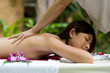A young woman having a back massage outside in tropical setting