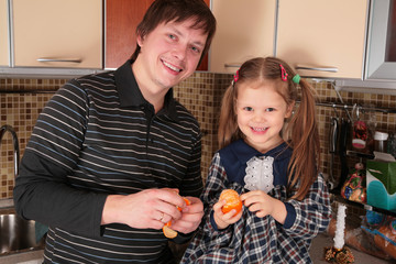 father and daughter with mandarins on the kitchen