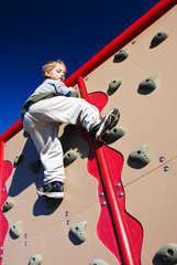 active boy scales a climbing wall