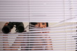Woman peering through blinds with binoculars
