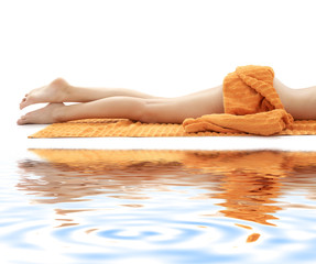 long legs of relaxed lady with orange towel on white sand #3