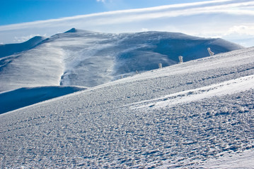 snow and ice covered terrain in mountains