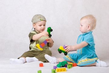 a boy and a girl of one and a half years old play the designer c